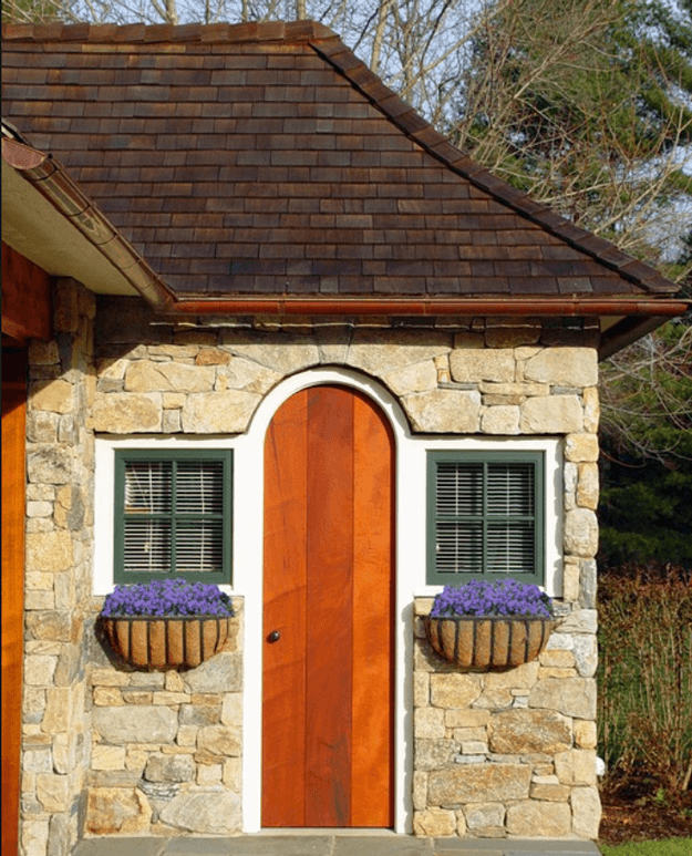 stone cottage with arched burnt orange wood door