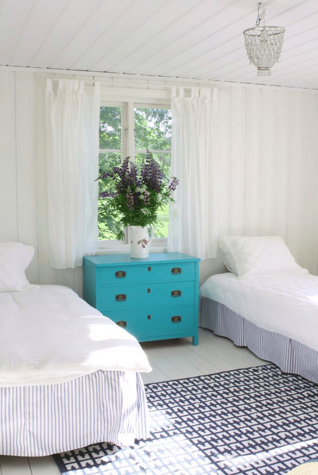 white bedroom with turquoise nightstand
