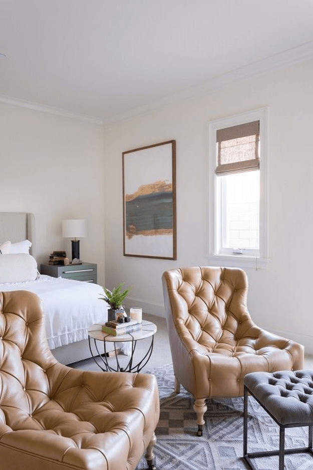 white bedroom with camel brown tufted chairs