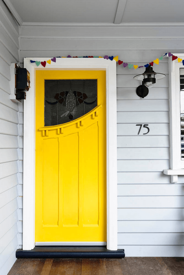 gray home white trim bright yellow door