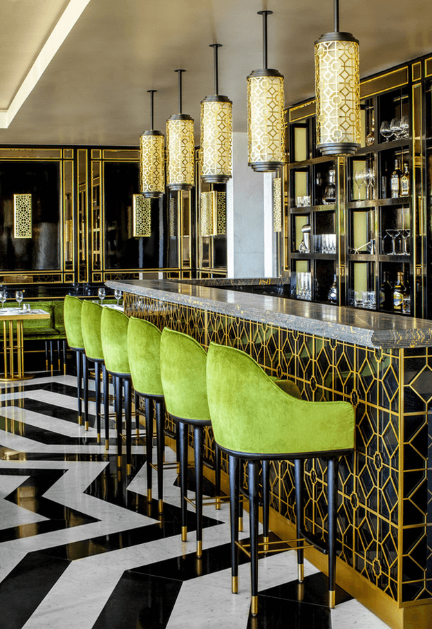 black white gold restaurant with bright green chairs