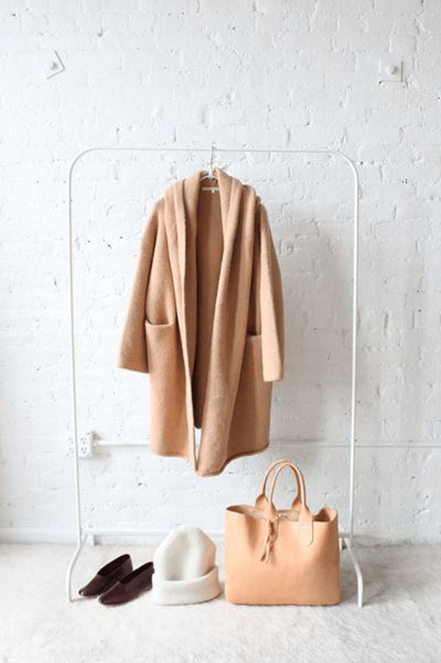 camel brown coat against white brick wall