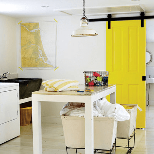 white laundry room with bright yellow barn door
