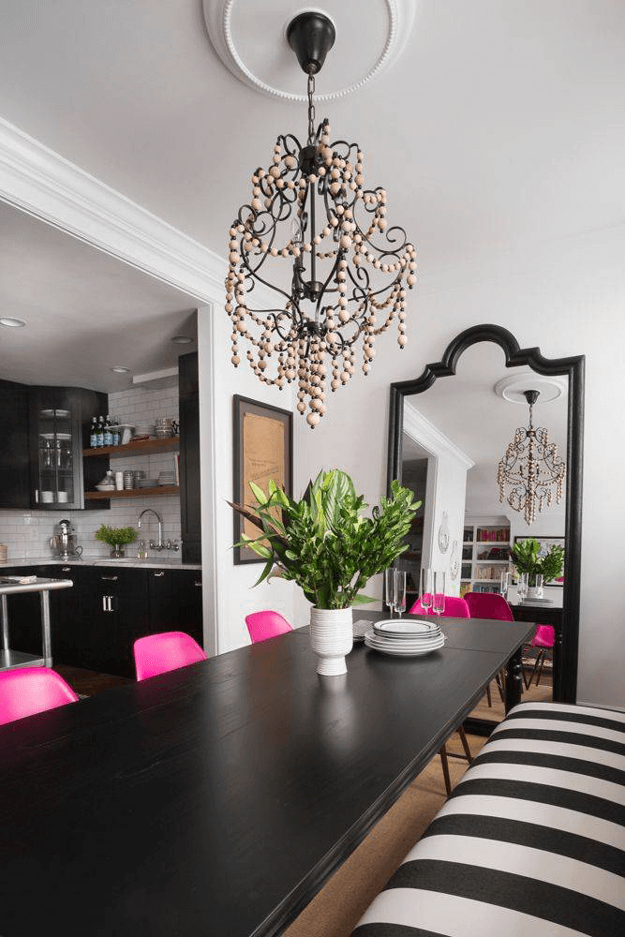 black and white dining room with hot pink chairs