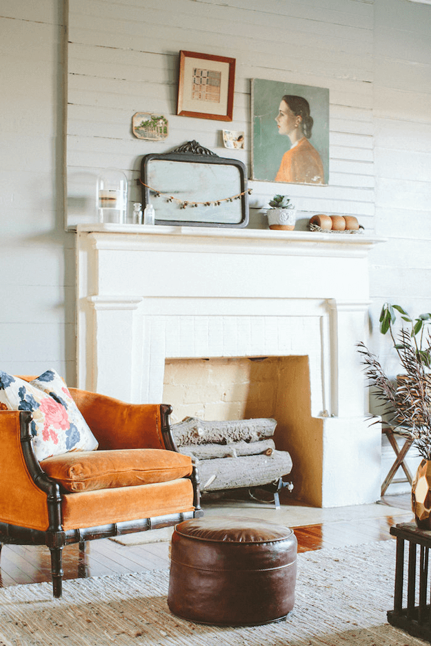 creamy white fireplace with burnt orange chair