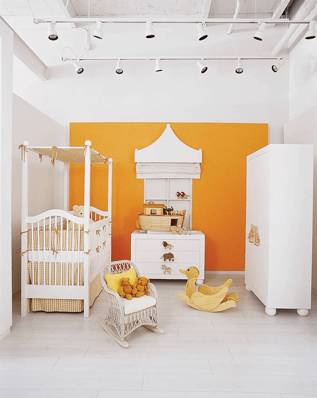 white modern nursery with orange accent wall