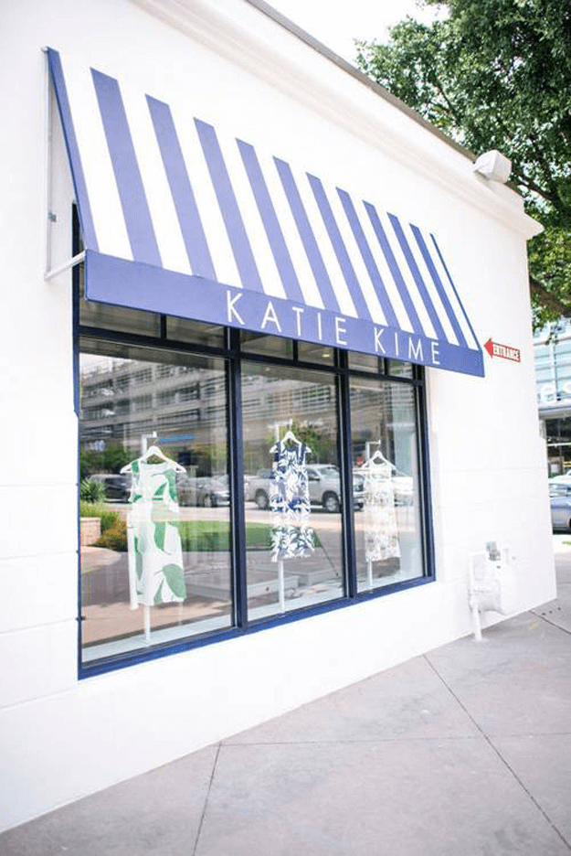 white storefront with periwinkle striped awning