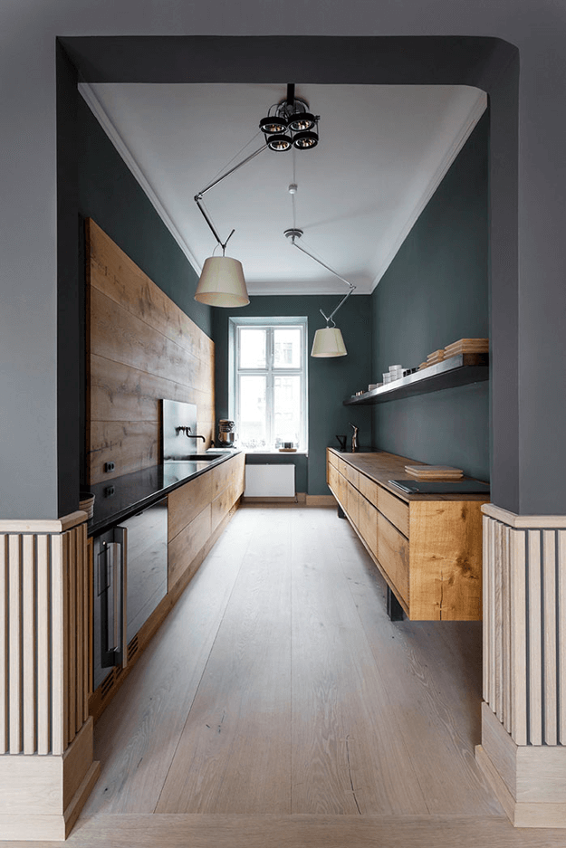 dark teal nordic style kitchen with light taupe wood floors