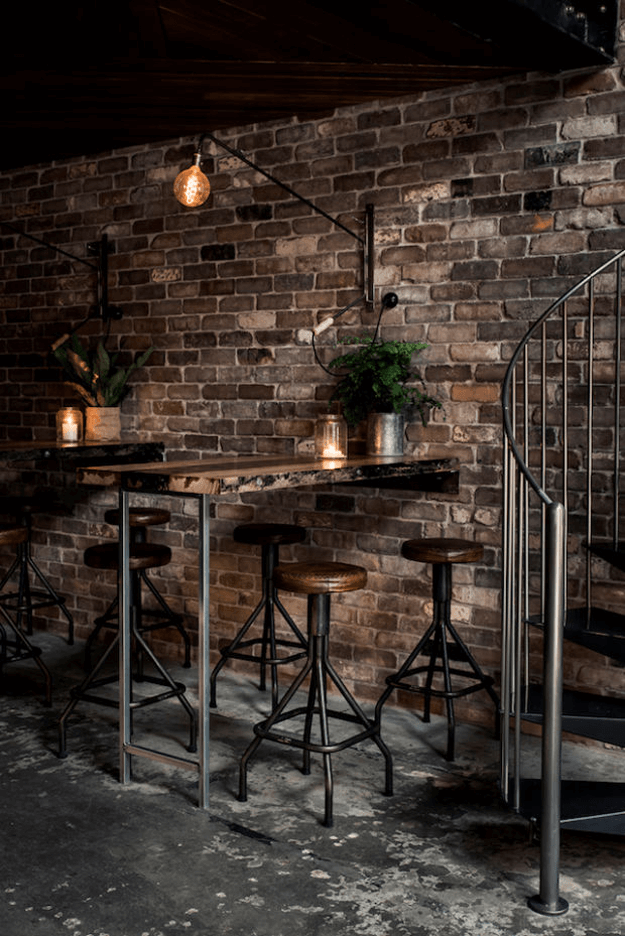 dark bronze bar interior with exposed brick wall