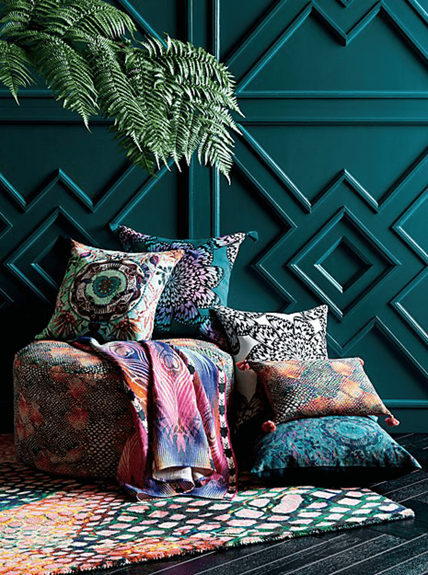 colorful pillow pile against teal green wall