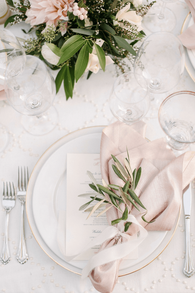 white table setting with pale pink and green accents