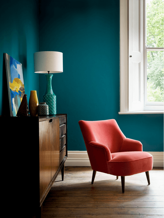 teal blue room with red chair