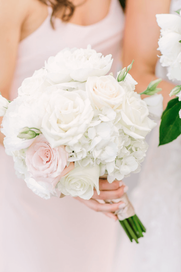 white bouquet with pale pink flowers and green accents