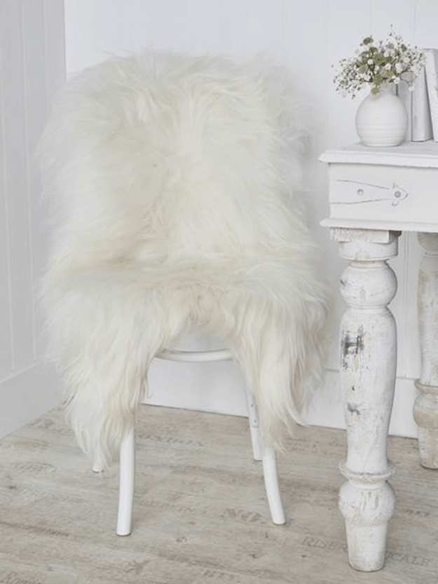 ivory white sheepskin rug draped over wood chair
