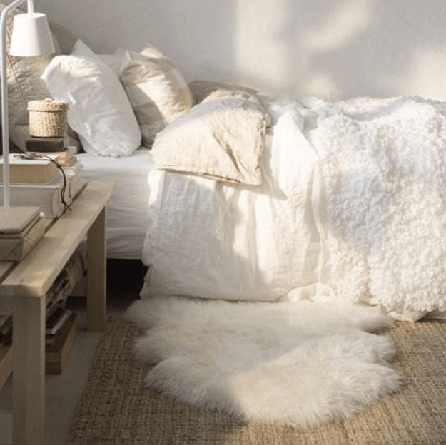 white sheepskin rug in natural toned bedroom
