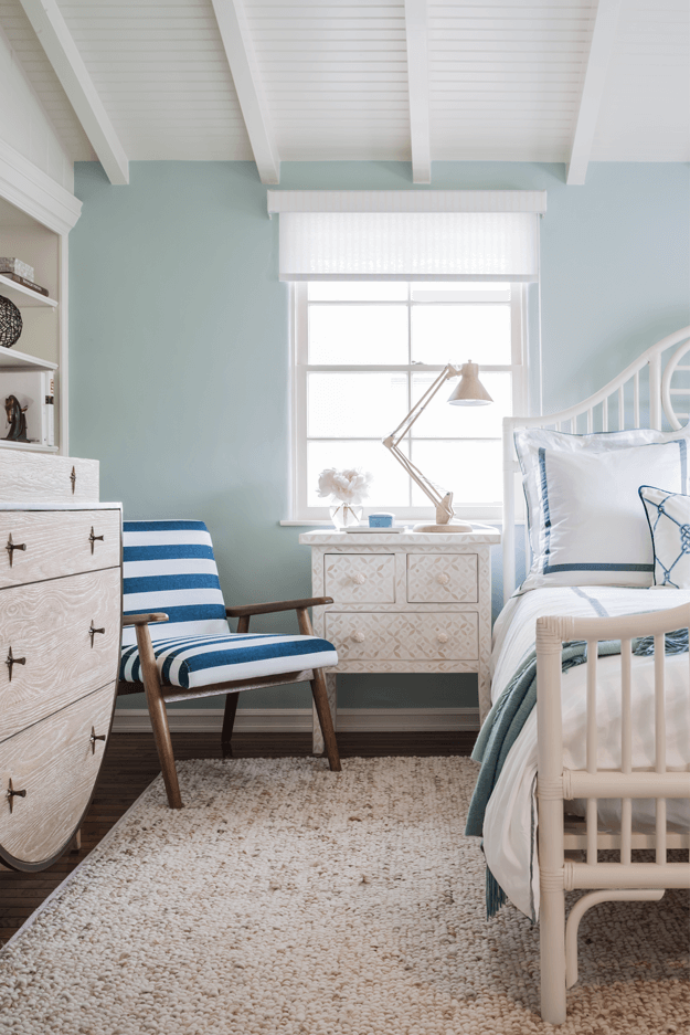 mint green coastal style bedroom with navy blue striped chair