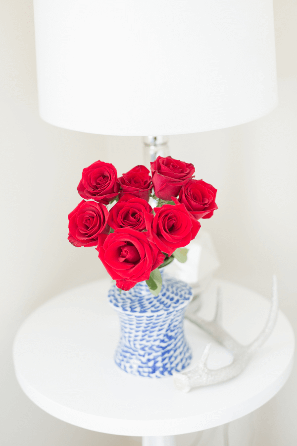 red roses in blue vase on white table