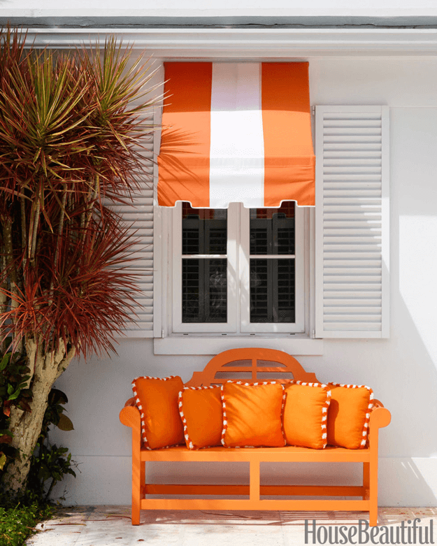 white home exterior with orange bench and striped awning