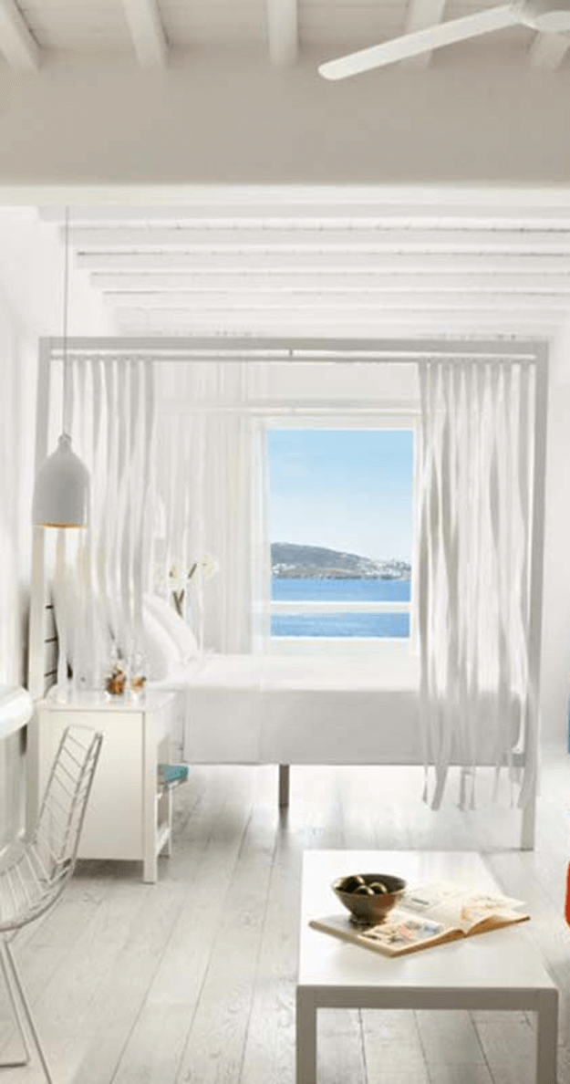 creamy white hotel bedroom with sea view