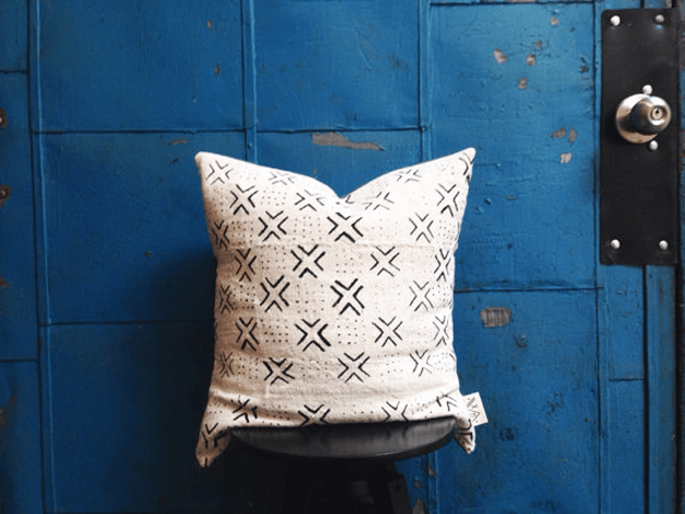white african mudcloth tribal pillow against blue door