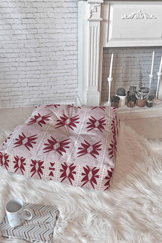burgundy and white floor pillow in white room
