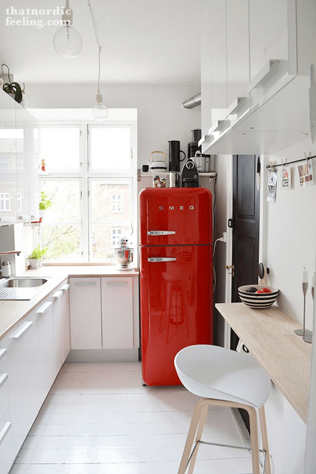white nordic style kitchen with bright red smeg fridge