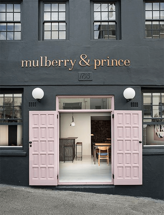 black restaurant exterior with blush pink doors