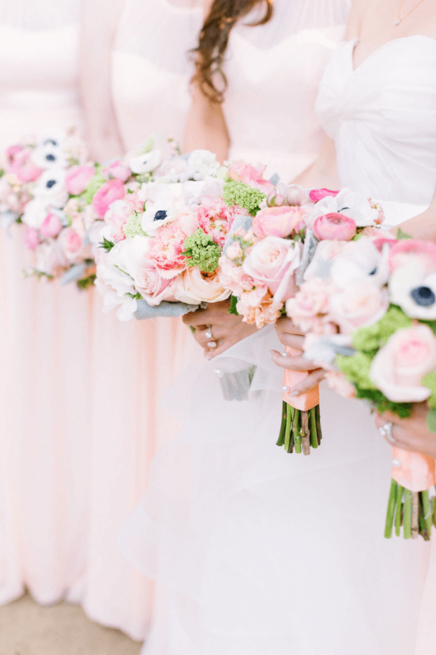 bridesmaids in pale pink dresses with colorful bouquets
