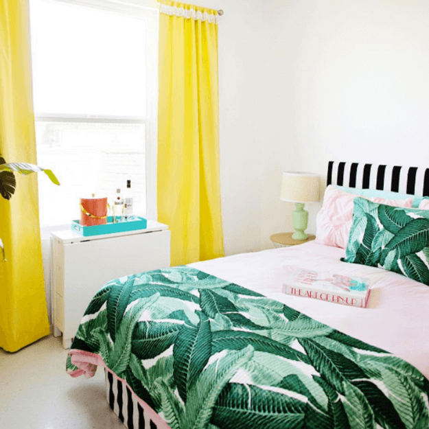 bedroom with banana leaf print and bright yellow curtains