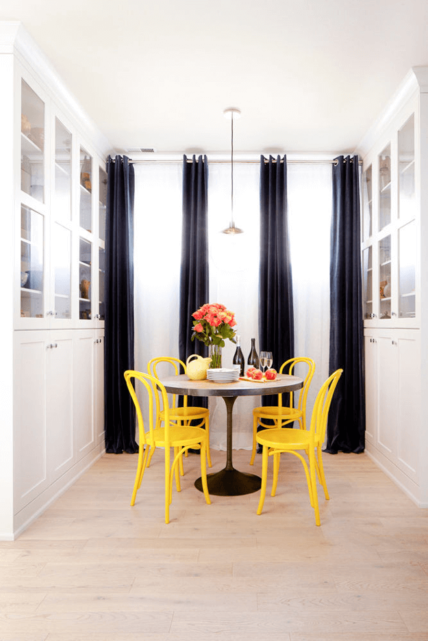 white dining room with bright yellow cafe chairs