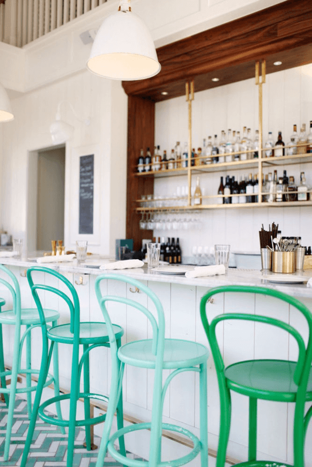 white bar interior with jade green cafe stools