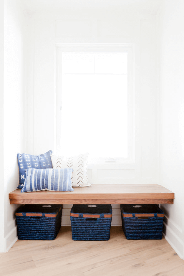 a bench seat styled with mudcloth pillows and indigo baskets, natural cherry bench, white oak flooring, white walls, white farmhouse interior