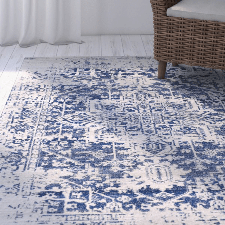 blue and beige oriental patterned rug on white floor, wicker chair, white curtains
