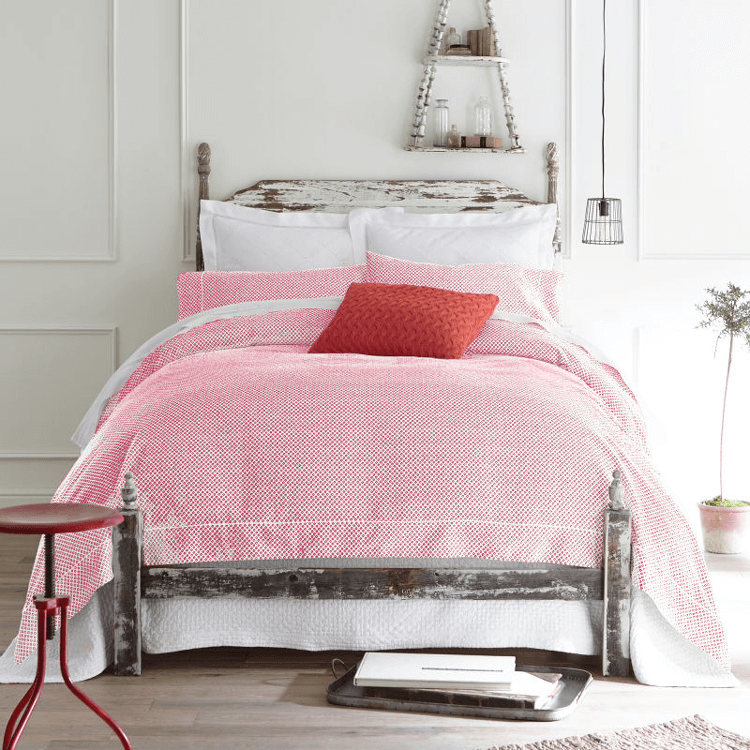 white bedroom with red bedding and vintage wood bed