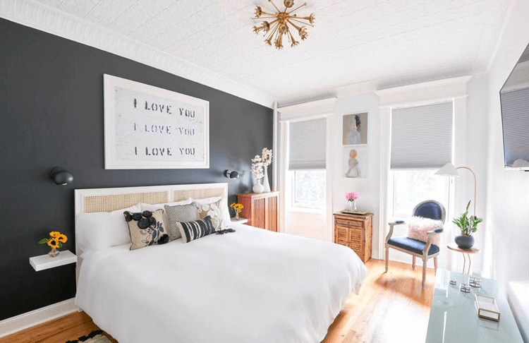 charcoal black accent wall, white bedroom, eclectic bedroom, honey oak flooring, oak flooring, white bedding, navy chair, pink sheep skin pillow, starburst light fixture, honeycomb shades